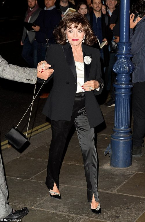 Suits you! Joan looked typically slick and suave in tailored fitted trousers and a black blazer, layered atop a crisp white shirt