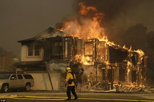 A firefighter walks near a home on fire in Santa Rosa after the entire area was evacuated