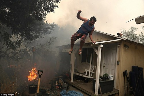 A resident rushes to save his home in Glen Ellen as an out-of-control wildfire moves through the area