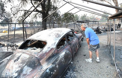 Napa resident Louis Reavis views his burned classic Oldsmobile at his home