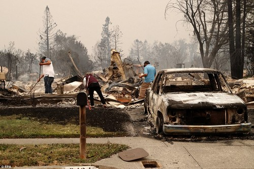 Residents go through their destroyed home as a burnt out car sits in the driveway. A total of 50,000 have been left without power