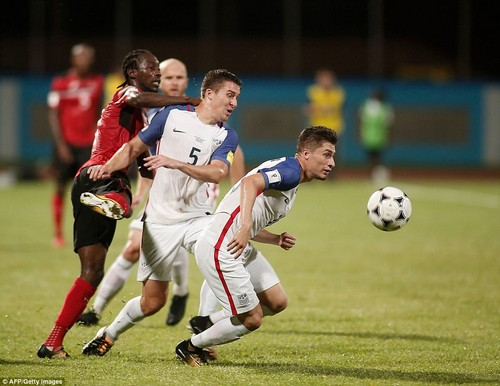 USA's Matt Besler (C) and USA's Jorge Villafana (R) vie for the ball with Trinidad and Tobago's Nathan Lewis (L) during their 2018 World Cup qualifier October 10, 2017