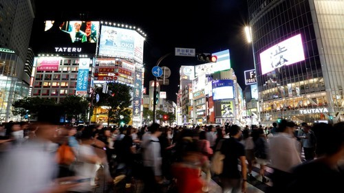 Pedestrians walk at a scramble crossing at Shibuya shopping district in Tokyo