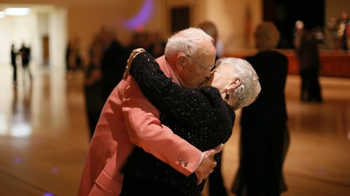 Donald Smitherman, 98, kisses his wife Marlene at the end of a dance in Sun City, Arizona, January 5, 2013. Sun City was built in 1959 by entrepreneur Del Webb as America?s first active retirement community for the over-55's. Del Webb predicted that retirees would flock to a community where they were given more than just a house with a rocking chair in which to sit and wait to die. Today?s residents keep their minds and bodies active by socializing at over 120 clubs with activities such as square dancing, ceramics, roller skating, computers, cheerleading, racquetball and yoga. There are 38,500 residents in the community with an average age 72.4 years. Picture taken January 5, 2013. REUTERS/Lucy Nicholson (UNITED STATES - Tags: SOCIETY)
