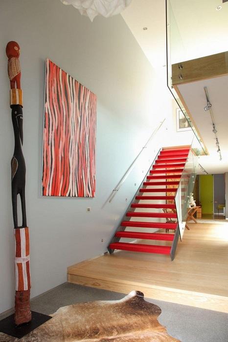 Красный цвет лестницы - яркая часть образа всего помещения.