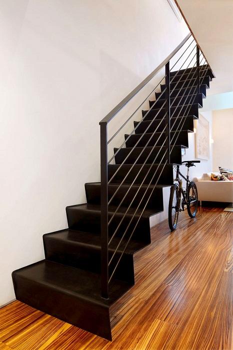 Массивная металлическая лестница с чёрными ступеньками и перилами, которая контрастным пятном выделяется на фоне светлого интерьера.