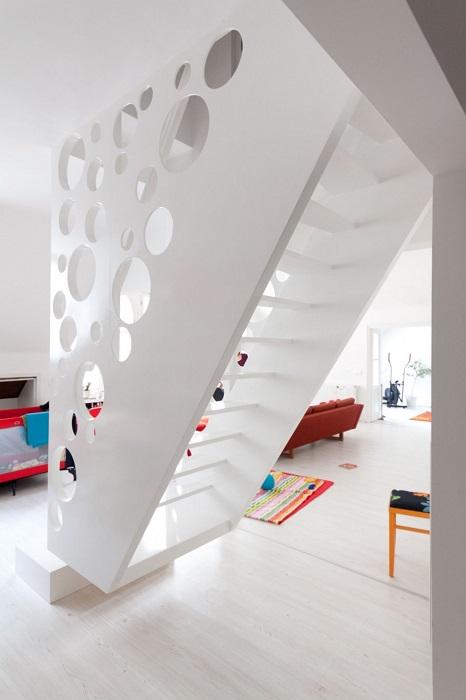 Необычная лестница из дерева, дизайн которой напоминает перфорированное полотно.