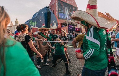 Fans, some from Mexico, do the limbo at the fan zone.
