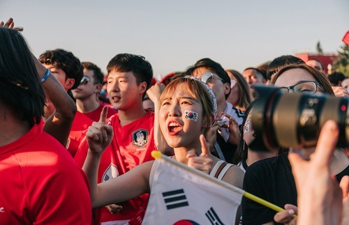 A Japan fan shows excitement, while a camera captures the scene.