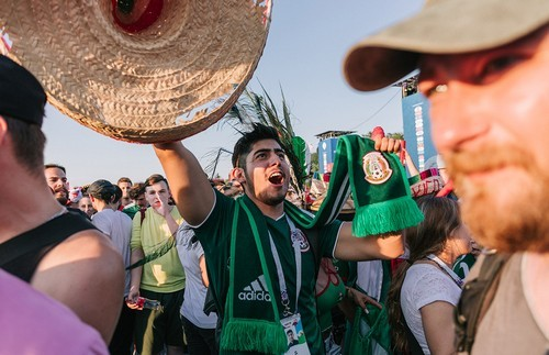 A fan from Mexico holds up his scarf and a hat at Moscow's fan zone.