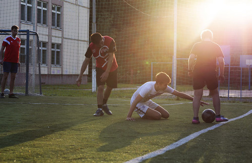 Young students scrimmage in the schoolyard while taking in the midsummer sun on a football pitch between the Tyoply Stan and Konkovo metros.