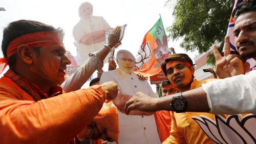 BJP supporters celebrate after learning the initial election results in New Delhi
