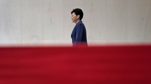 Hong Kong Chief Executive Carrie Lam walks behind a red barrier tape toward a press conference in Hong Kong Monday, June 10, 2019