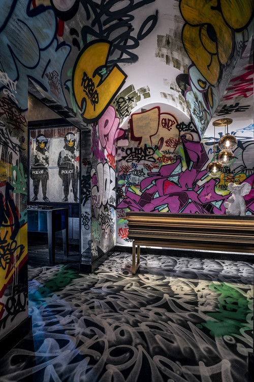 """The tunnel painted byCes, and Banksy's""""Smiley Coppers Panel I"""" on the left."""