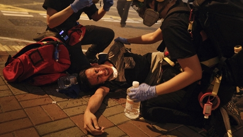 Medical workers help a protester in pain from tear gas fired by policemen on a street in Hong Kong, Sunday, July 21, 2019. Hong Kong police have thrown tear gas canisters at protesters after they refu
