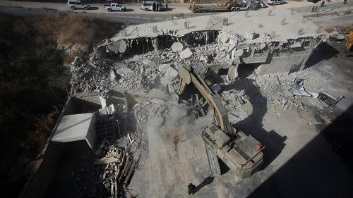 Israeli forces destroy a building in a Palestinian village of Sur Baher, east Jerusalem, Monday, July 22, 2019. Israeli work crews have begun demolishing dozens of Palestinian homes in an east Jerusal