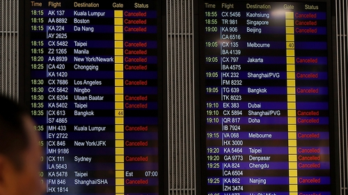 A man looks at the flight information board shows outbound flights was cancel at the Hong Kong International airport, Monday, Aug. 12, 2019. One of the world's busiest airports cancelled all remaining
