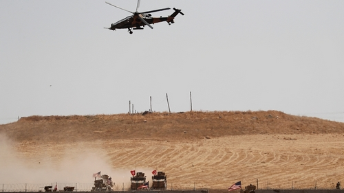 Turkish military helicopter flies over as Turkish and U.S. troops return from a joint U.S.-Turkey patrol in northern Syria, as it is pictured from near the Turkish town of Akcakale, Turkey,