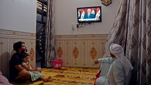 Iraqis watch a televised speech by Iraq's President Barham Saleh in the central holy shrine city of Najaf on October 31, 2019. - Saleh vowed to hold early parliamentary elections once a new law is pas